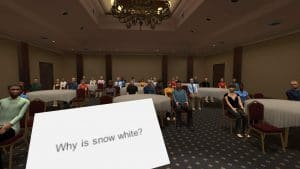 "A presentation in a large room with round tables. An impromptu topic on a notecard is visible, ""Why is snow white?"""